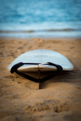 Surfboard with leash on sand with ocean in background